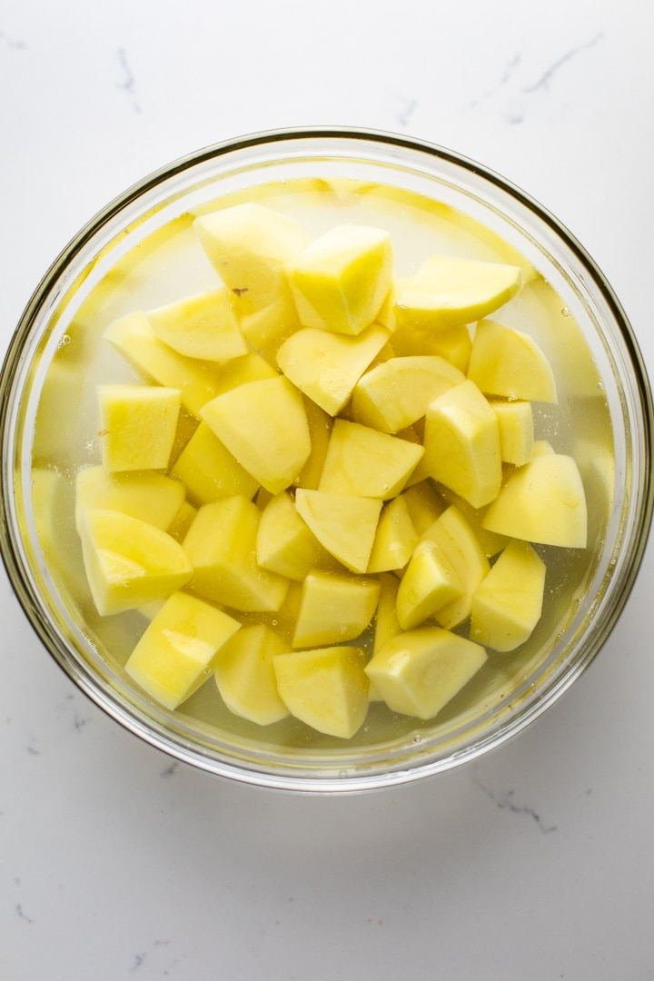 A clear bowl with chopped potatoes and water in it.