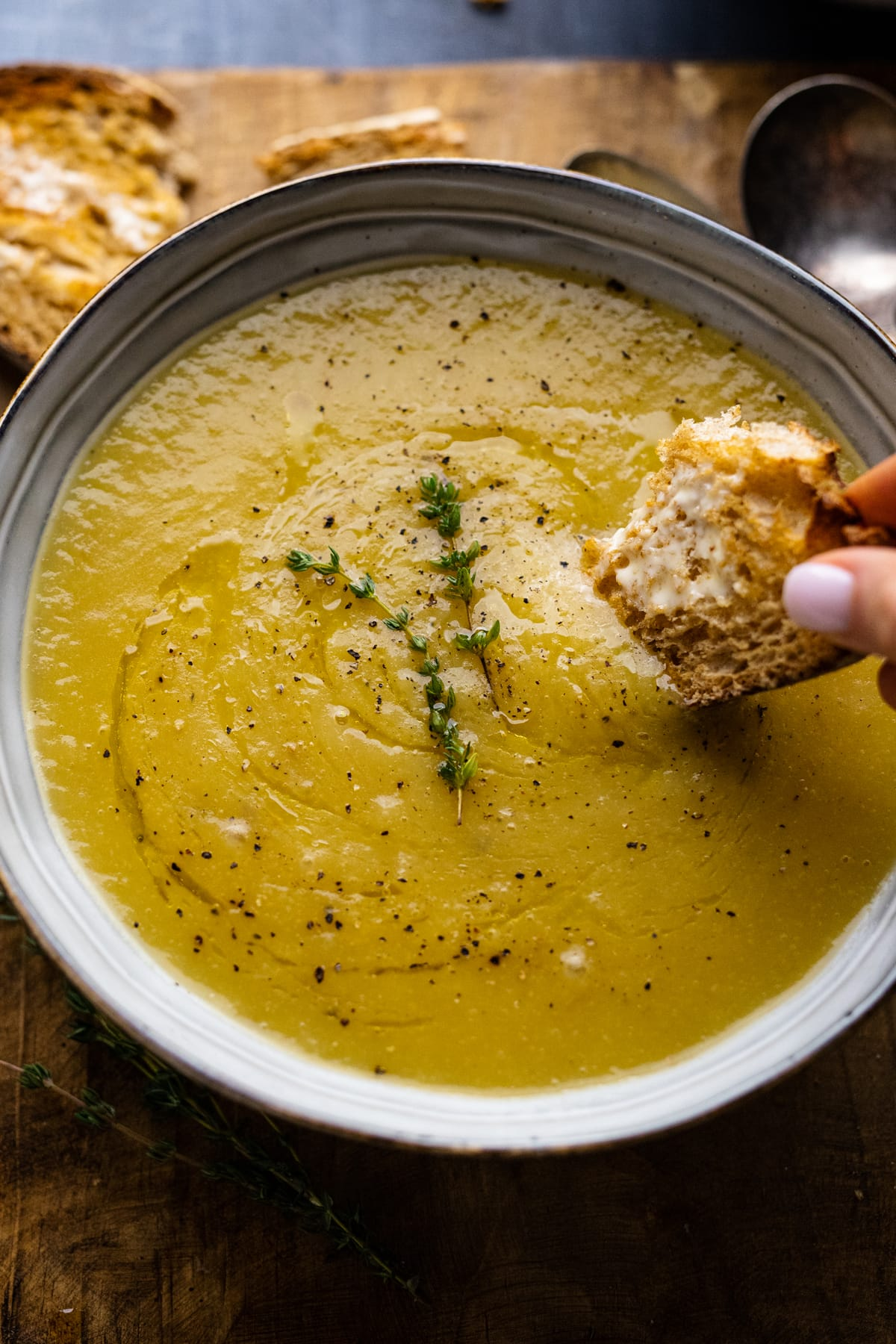 A hand dipping bread into a bowl of leek and potato soup.