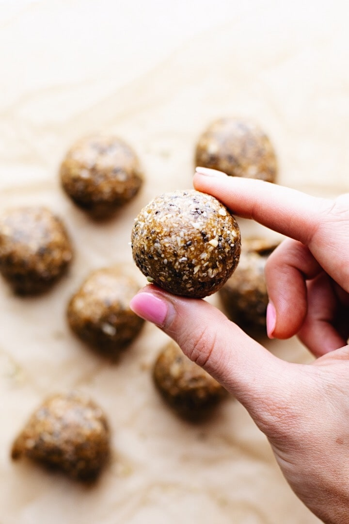 A hand holding oatmeal protein ball with protein balls in the background.