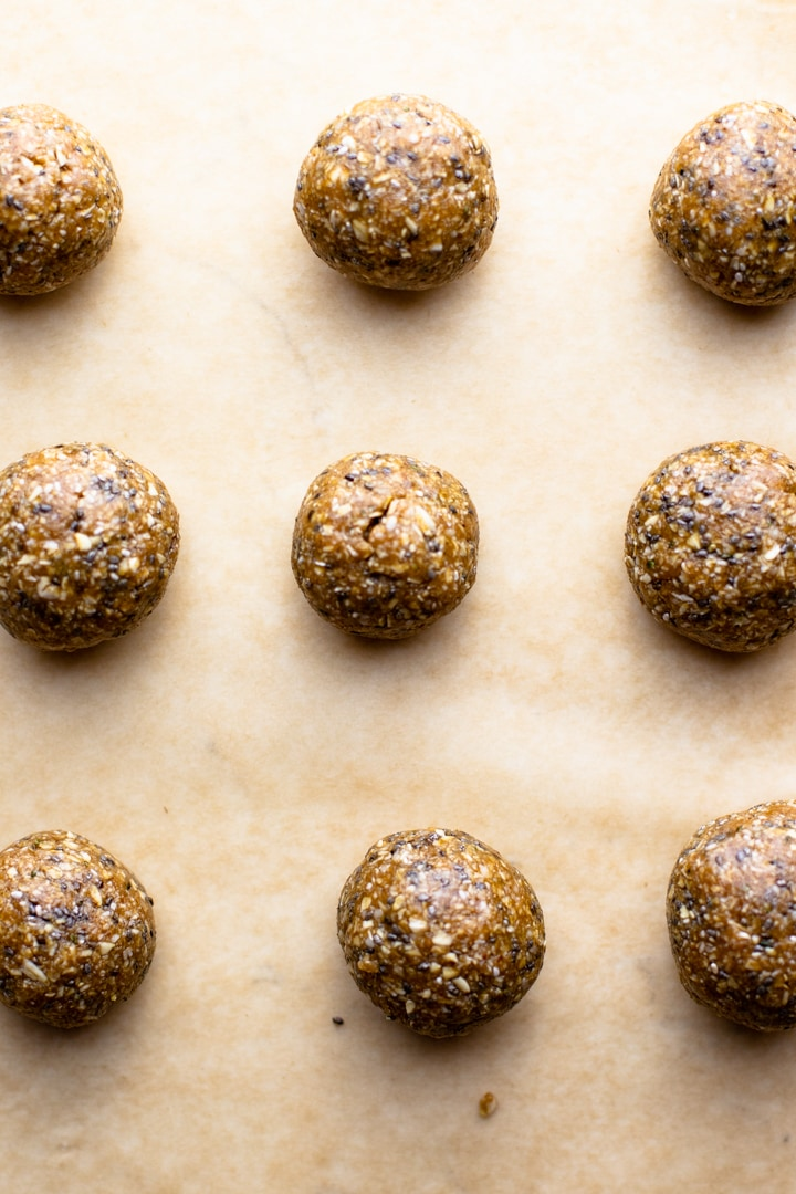oatmeal protein balls on a sheet pan with brown parchment paper.