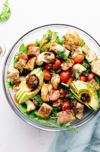 A clear bowl on a white counter with Panzanella salad.