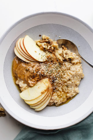 Apple cinnamon oatmeal in a light grey ceramic bowl with a spoon in it.