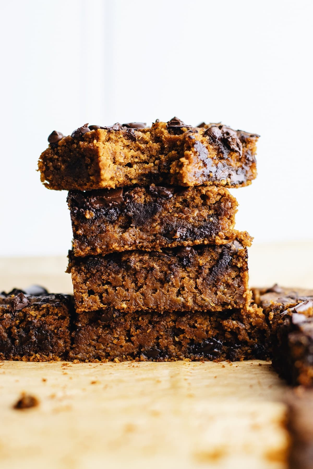 Four pumpkin blondies stacked on top of each other one with a bite out of it.