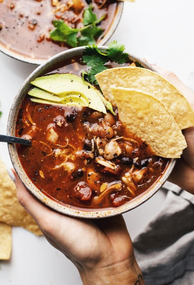 Hands holding a ceramic bowl with slow cooker chicken chili in it with tortilla chips and avocado slices over top.