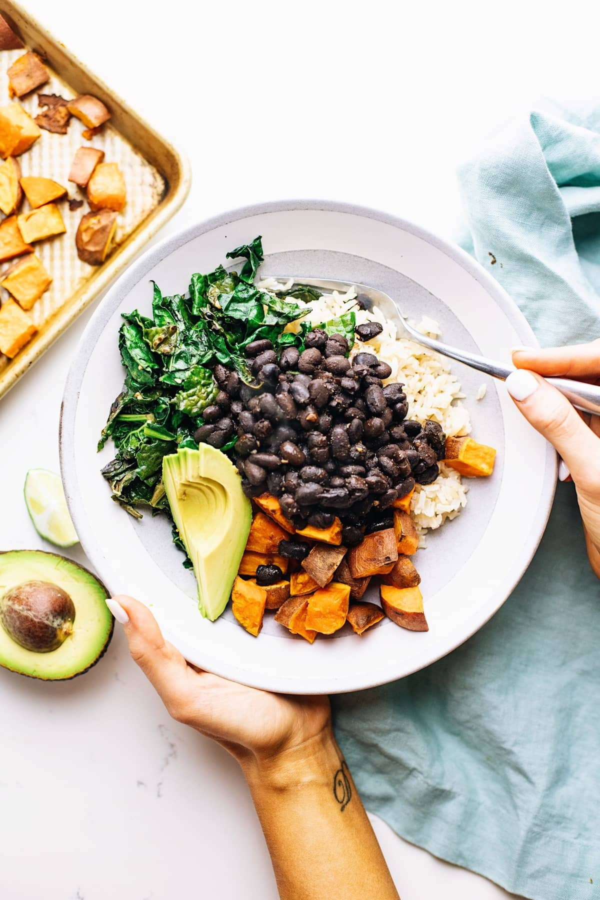 Hands holding a grey ceramic bowl with sweet potatoes and black beans in it with a blue napkin and food in the background.