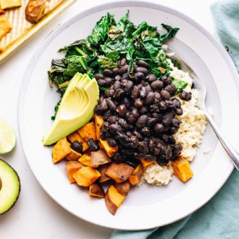 A ceramic bowl with black beans, greens, and sweet potatoes in it with a blue napkin next to it.