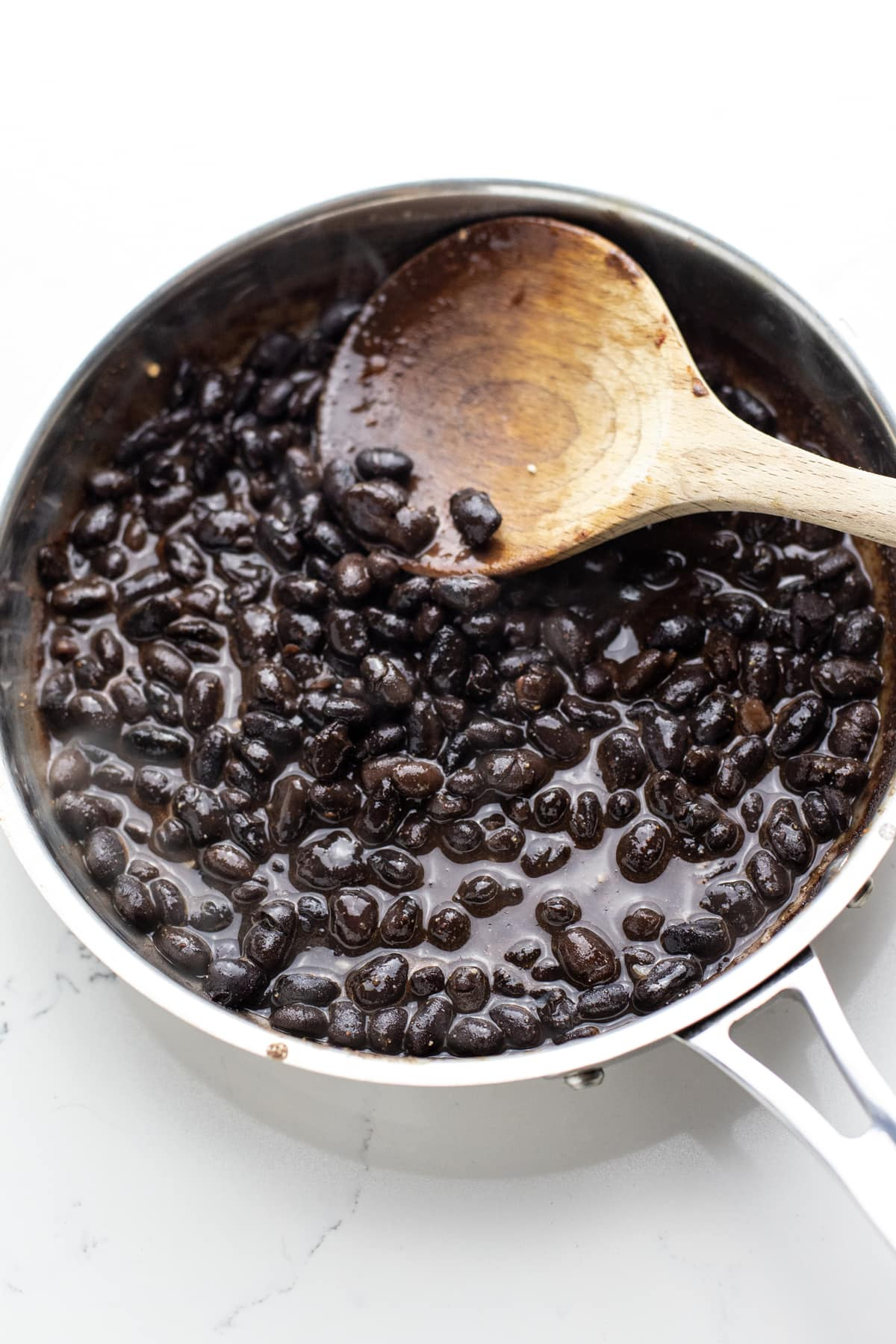 Black beans cooking in a silver pan with a wooden spoon in it.