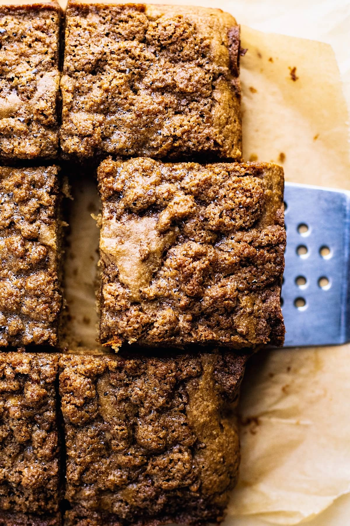 A spatula picking up a slice of banana coffee cake on brown parchment paper.