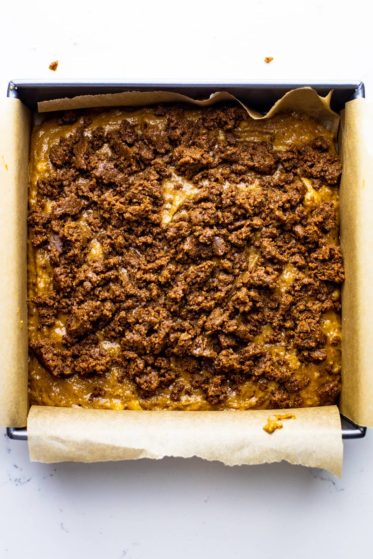 A square 8x8 inch pan with coffee cake batter in it and crumble over top.