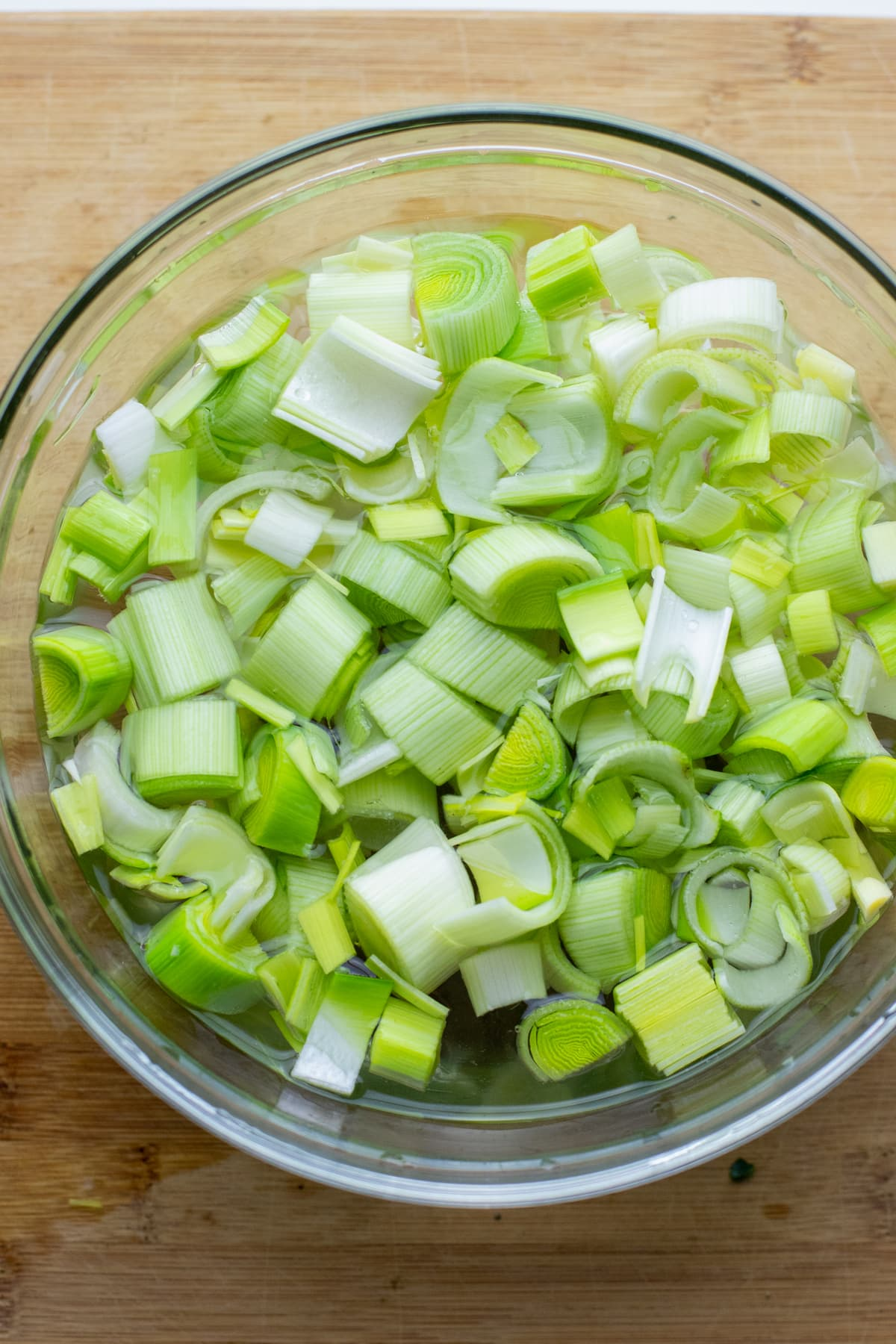 A clear glass bowl with chopped leeks soaking in water with a cutting board in the background.