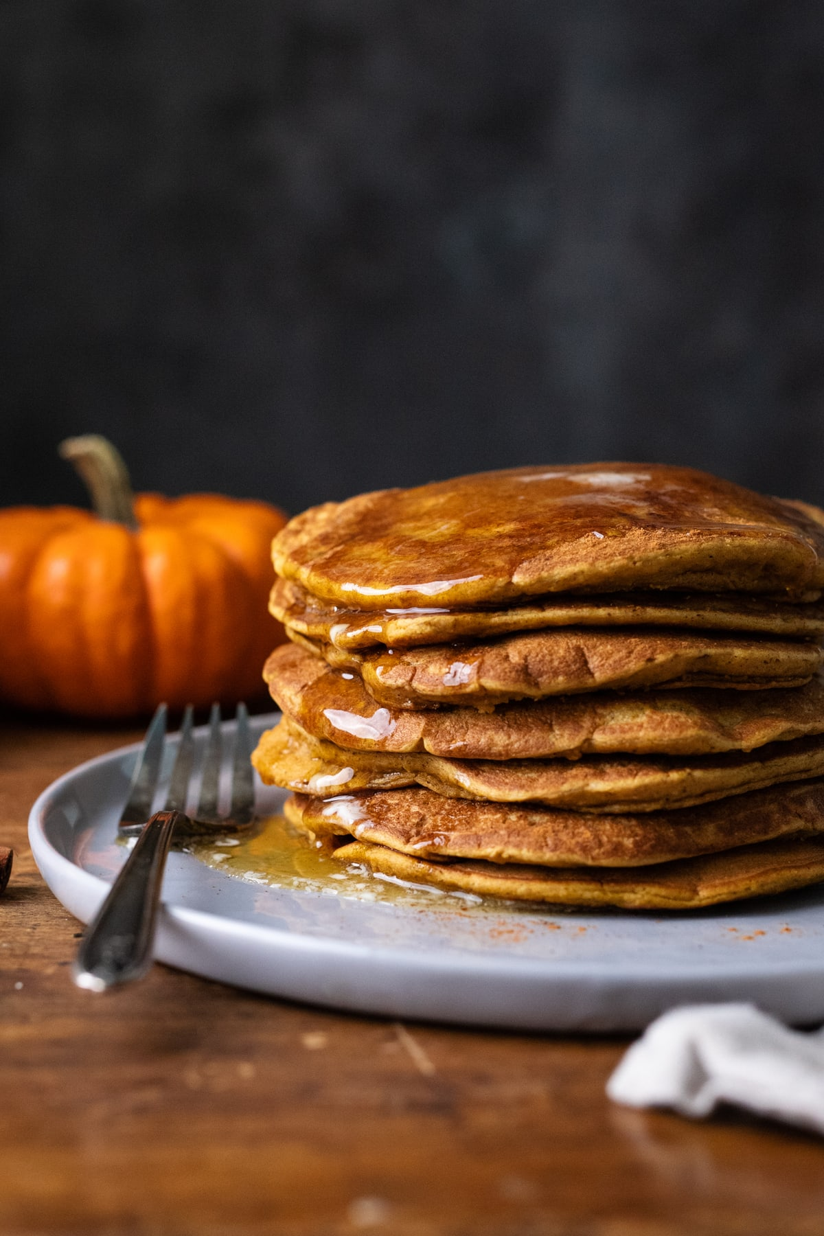 A stack of pumpkin spice pancakes on a gray plate with a fork laying next to the pancakes and an orange pumpkin in the background.