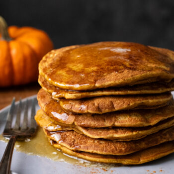 A stack of pumpkin spice pancakes on a gray plate with a fork next to it. Behind the plate of pancakes is a orange pumpkin and a dark background.