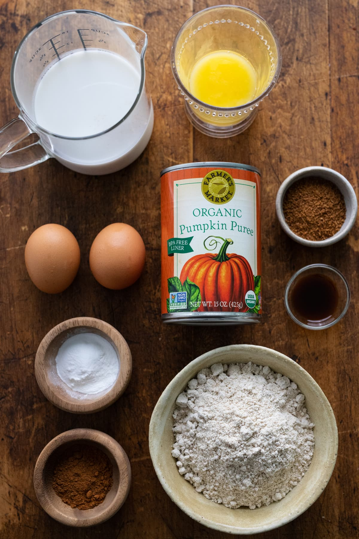 Ingredients for healthy pumpkin spice pancakes arranged on a wooden background.