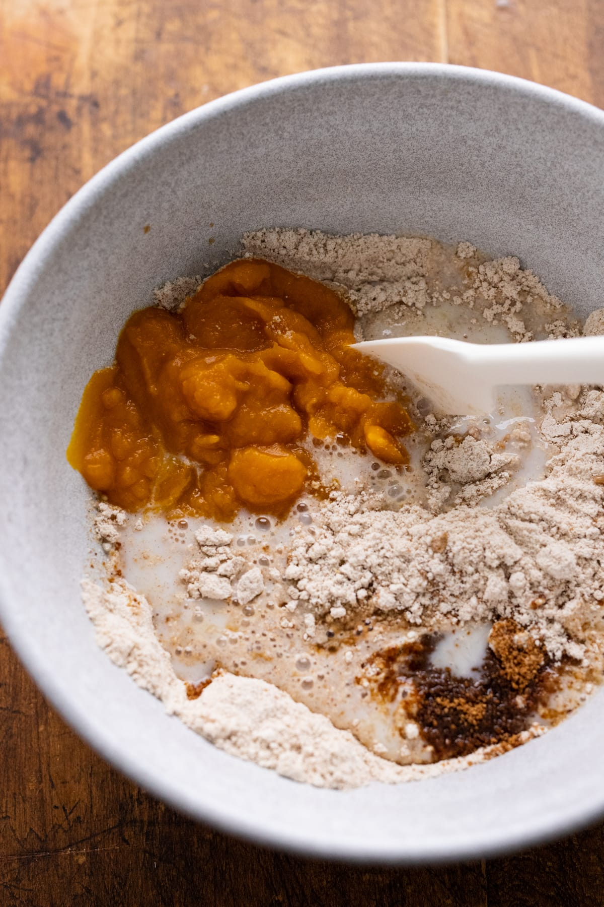 Ingredients for pumpkin pancakes being stirred in a white bowl with a rubber spatula.