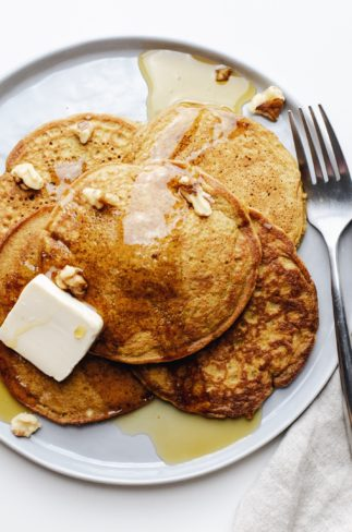 A close up of a stack of pumpkin spice pancakes with butter, drizzled maple syrup, and a fork next to it.