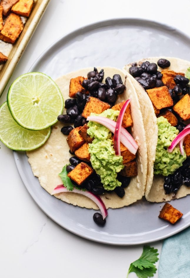A close up of sweet potato black bean tacos on a grey plate with lime slices next to it.