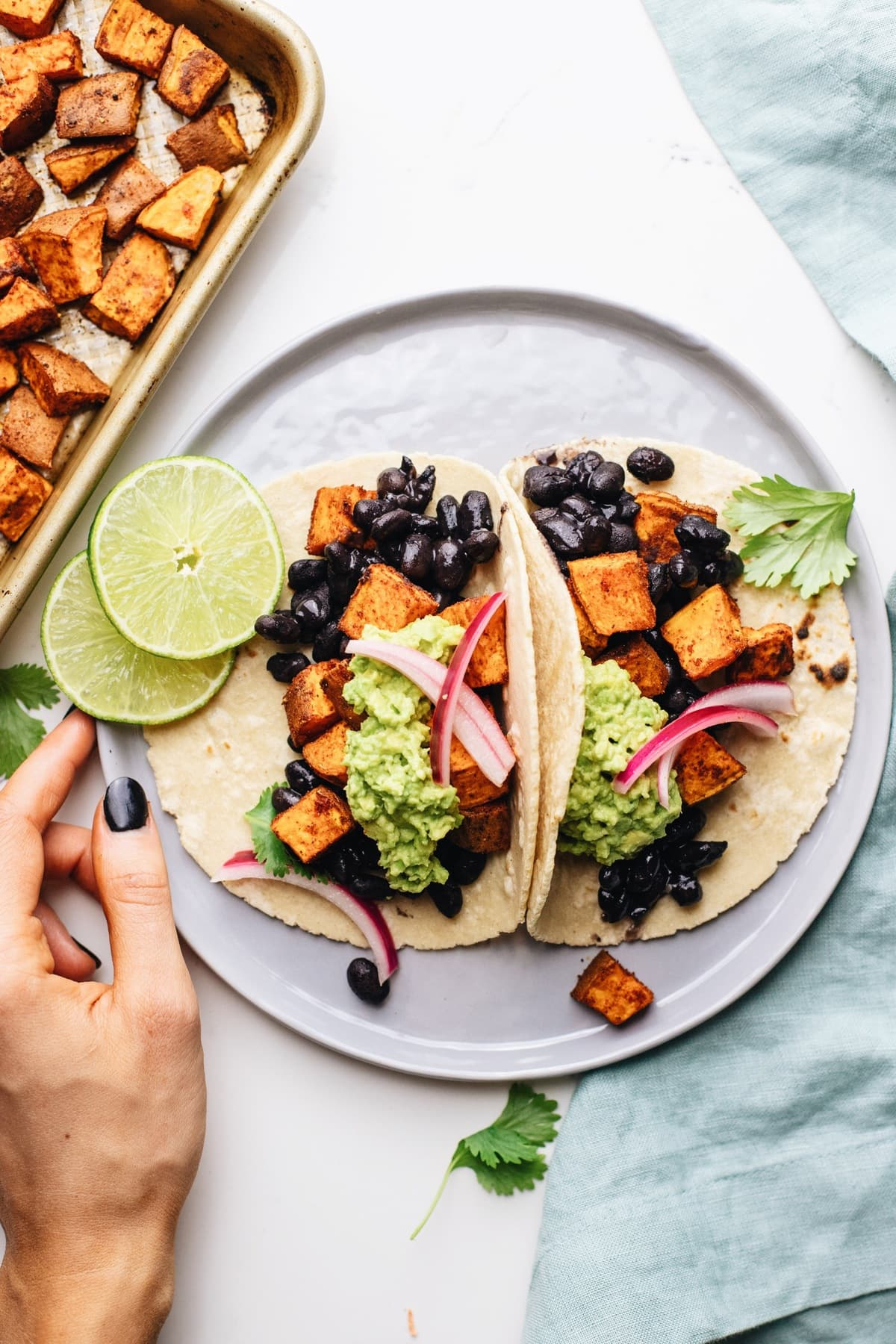 A hand holding a grey plate with sweet potato black bean tacos with a blue napkin next to it.