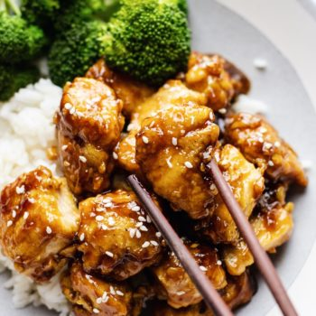 A close up of chopsticks picking up a piece of honey sesame chicken with broccoli and rice in the background.