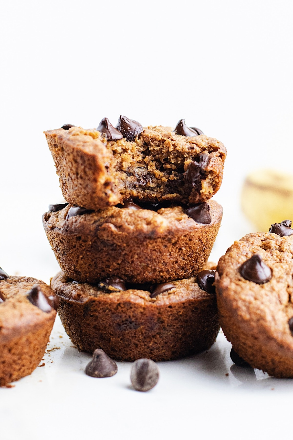 Chocolate chip vegan banana muffins stacked on top of each other one with a bite out of it.