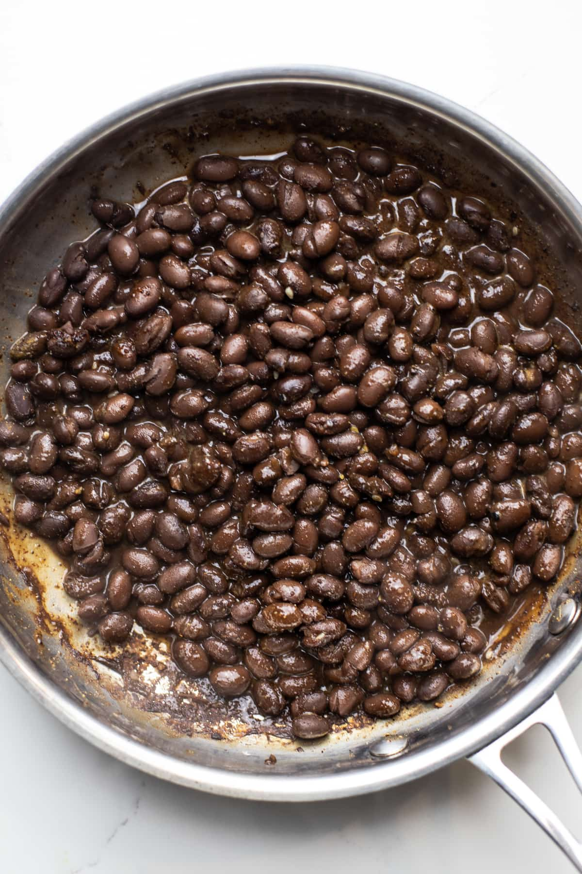 A stainless steal pan with black beans cooking in it.
