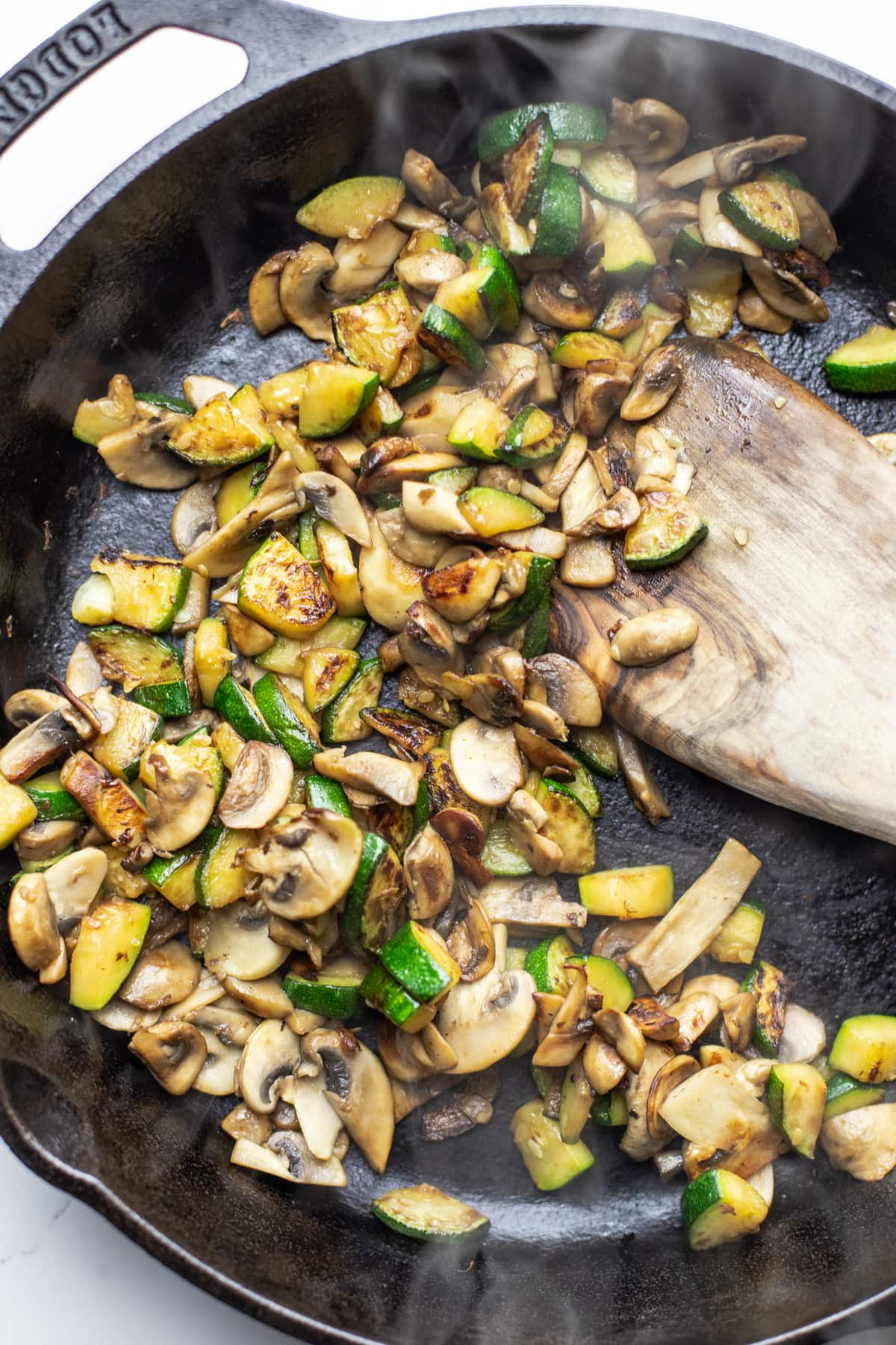 A wooden spoon stirring sauteed mushrooms and zucchini in a black cast iron skillet.