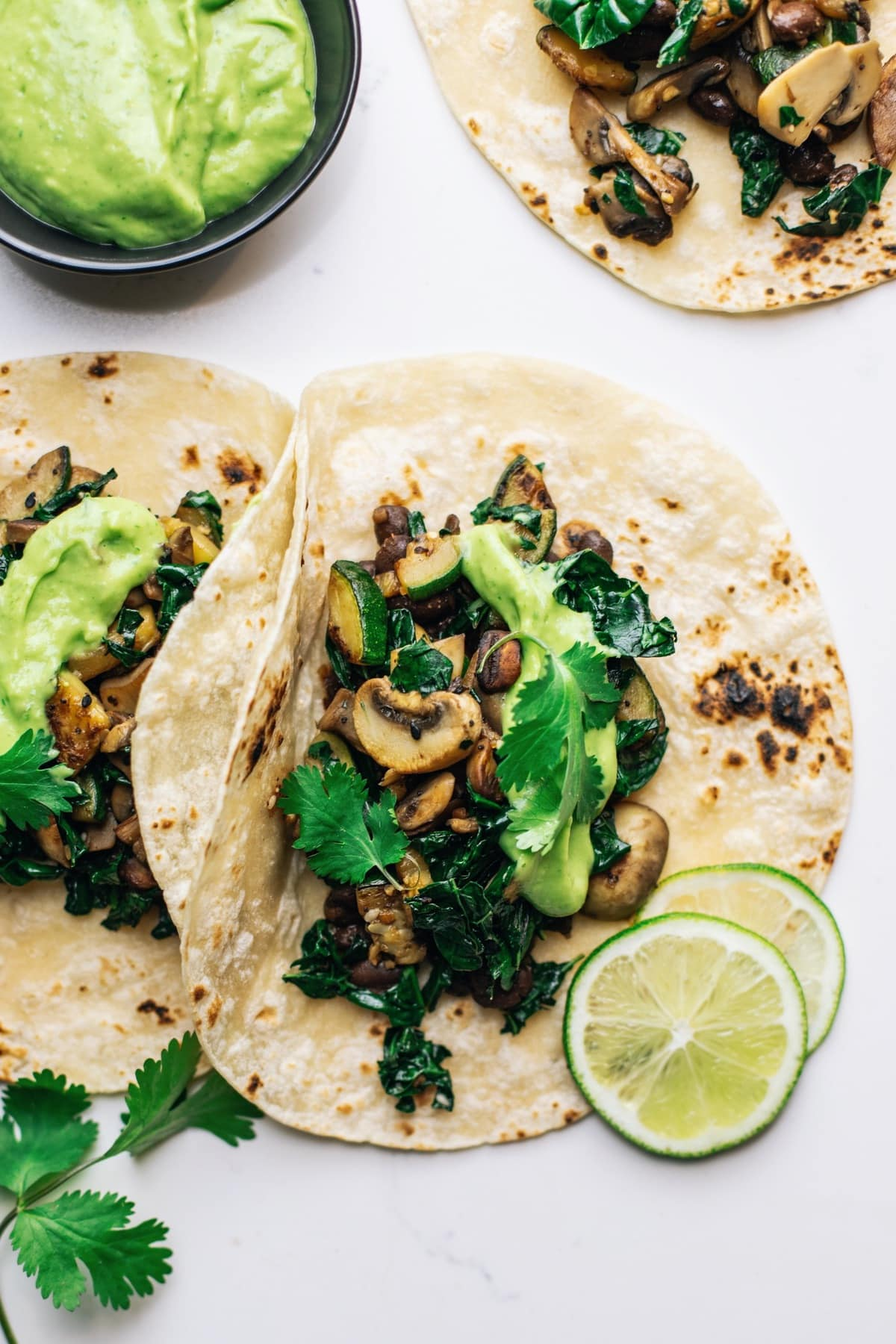 Veggie tacos on a white counter with avocado sauce and lime slices arranged around them.