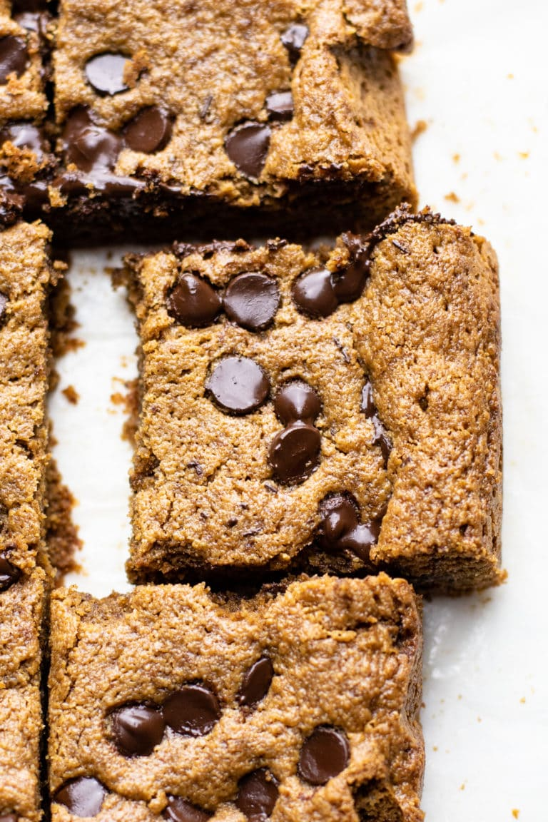 A close up image of chocolate chip oatmeal bar on white parchment paper.