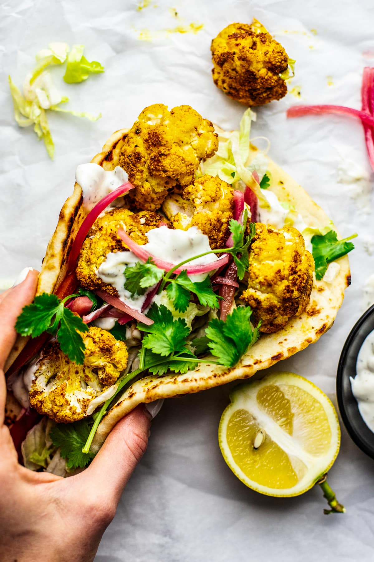 hand holding naan cauliflower shawarma wrap won white parchment paper with condiments arranged around it.