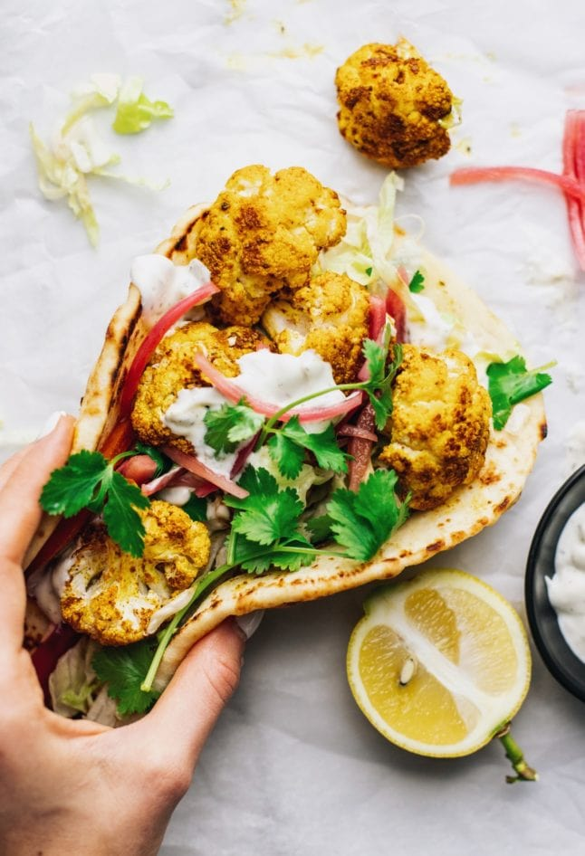 A hand holding a naan wrap with roasted cauliflower on white parchment paper.