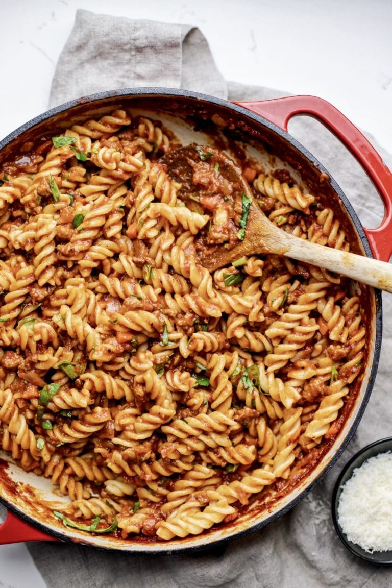 A red pan with pasta noodles and sauce with a wooden spoon in it.