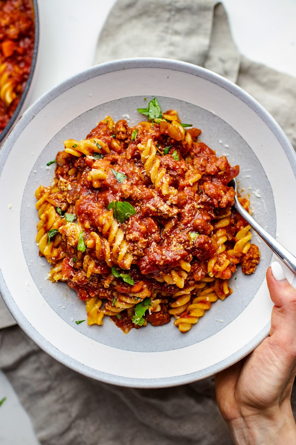 hand holding ceramic bowl with fusilli pasta noodles mixed with red sauce.