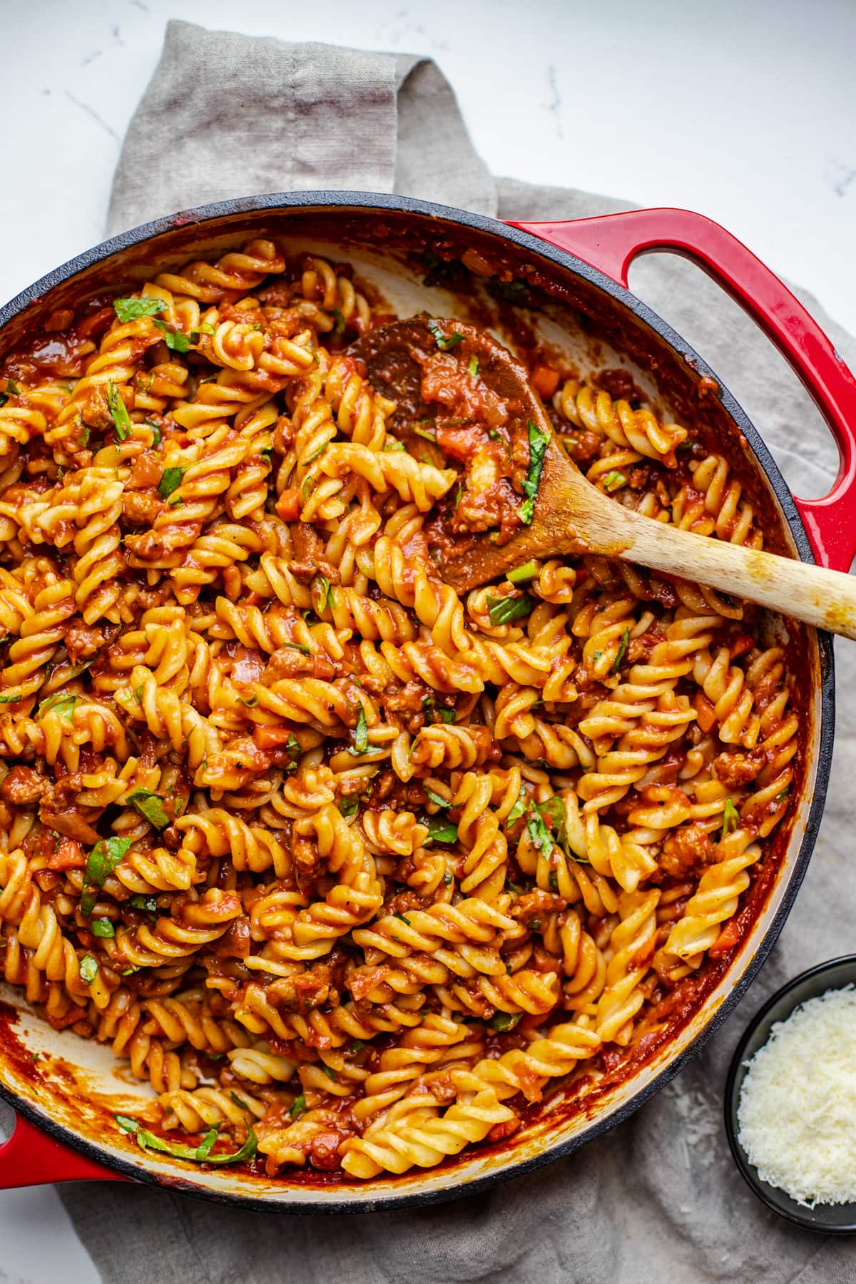 red pan with fusilli noodles in it with a wooden spoon.