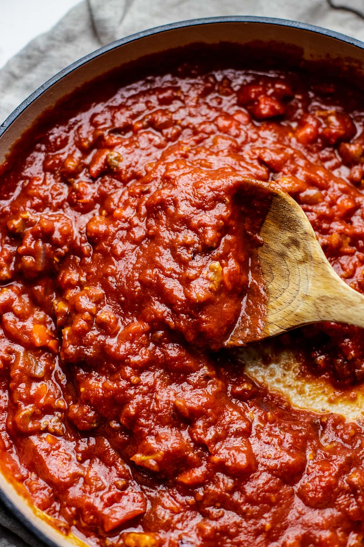 wooden spoon stirring red sauce.