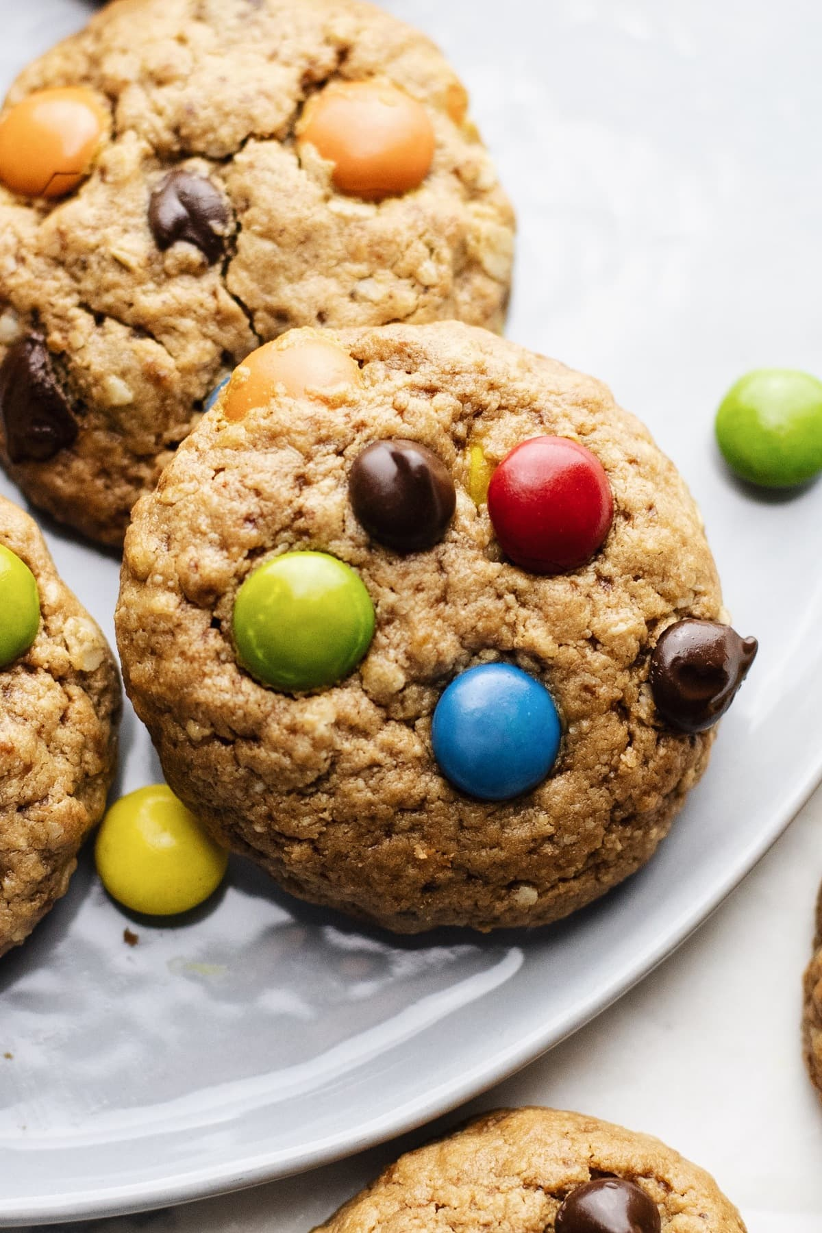 a close up of a m&m and chocolate chip cookie on a grey plate.