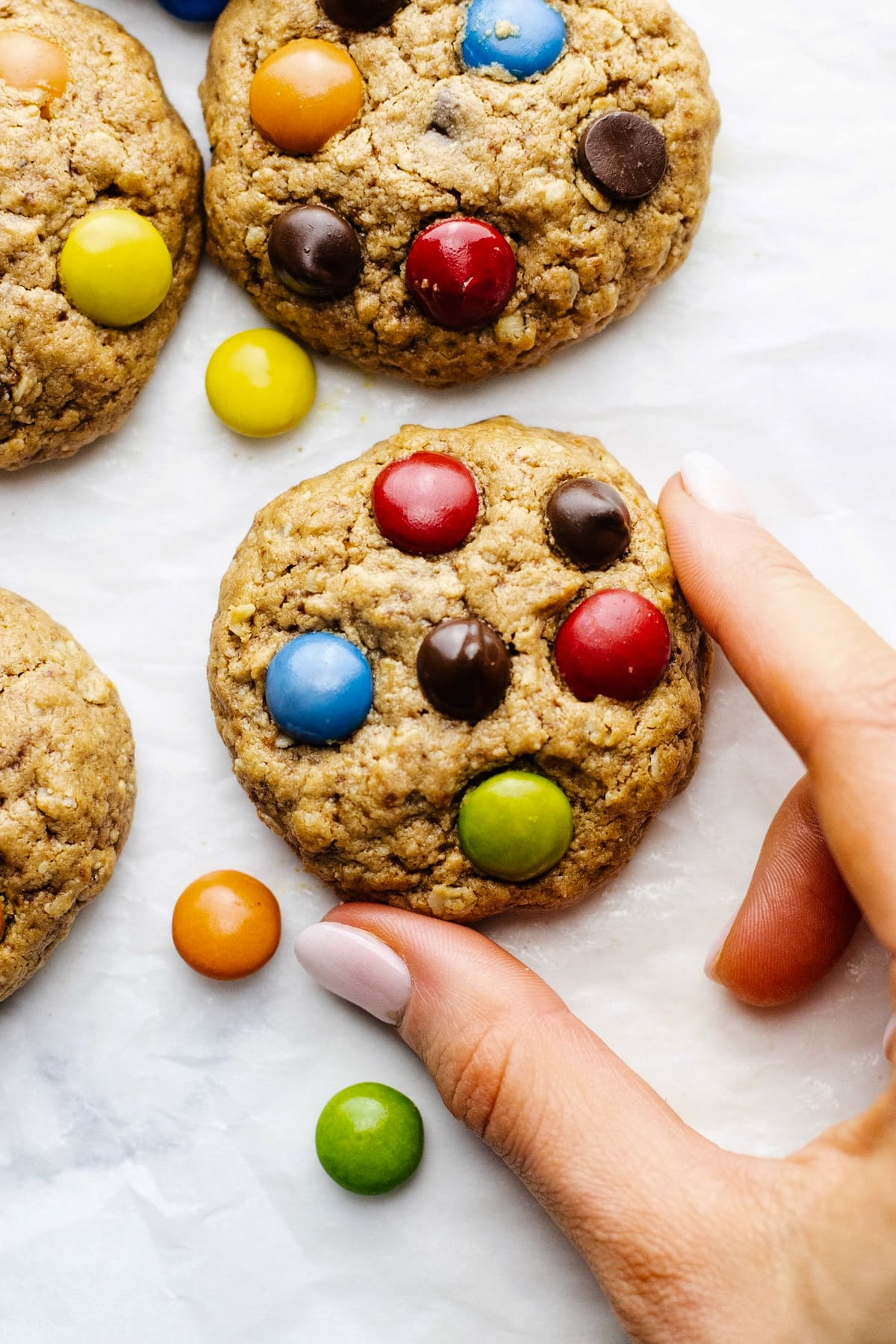 A hand holding a m&m and chocolate chip cookie on a white counter.