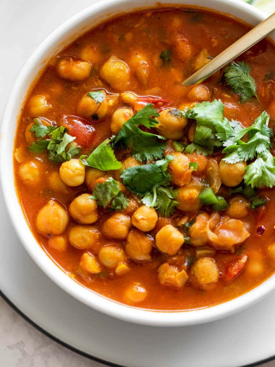 A white bowl with chana masala and cilantro leaves on top.