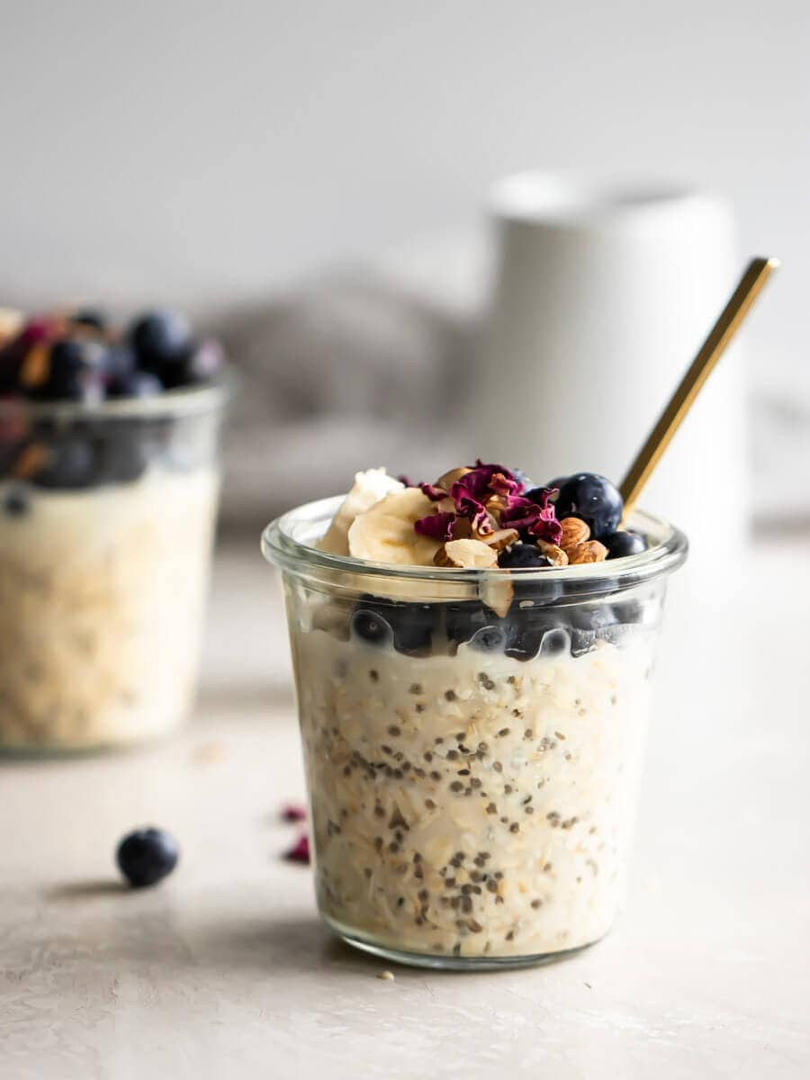 a glass jar with overnight oats with a jar in the background.