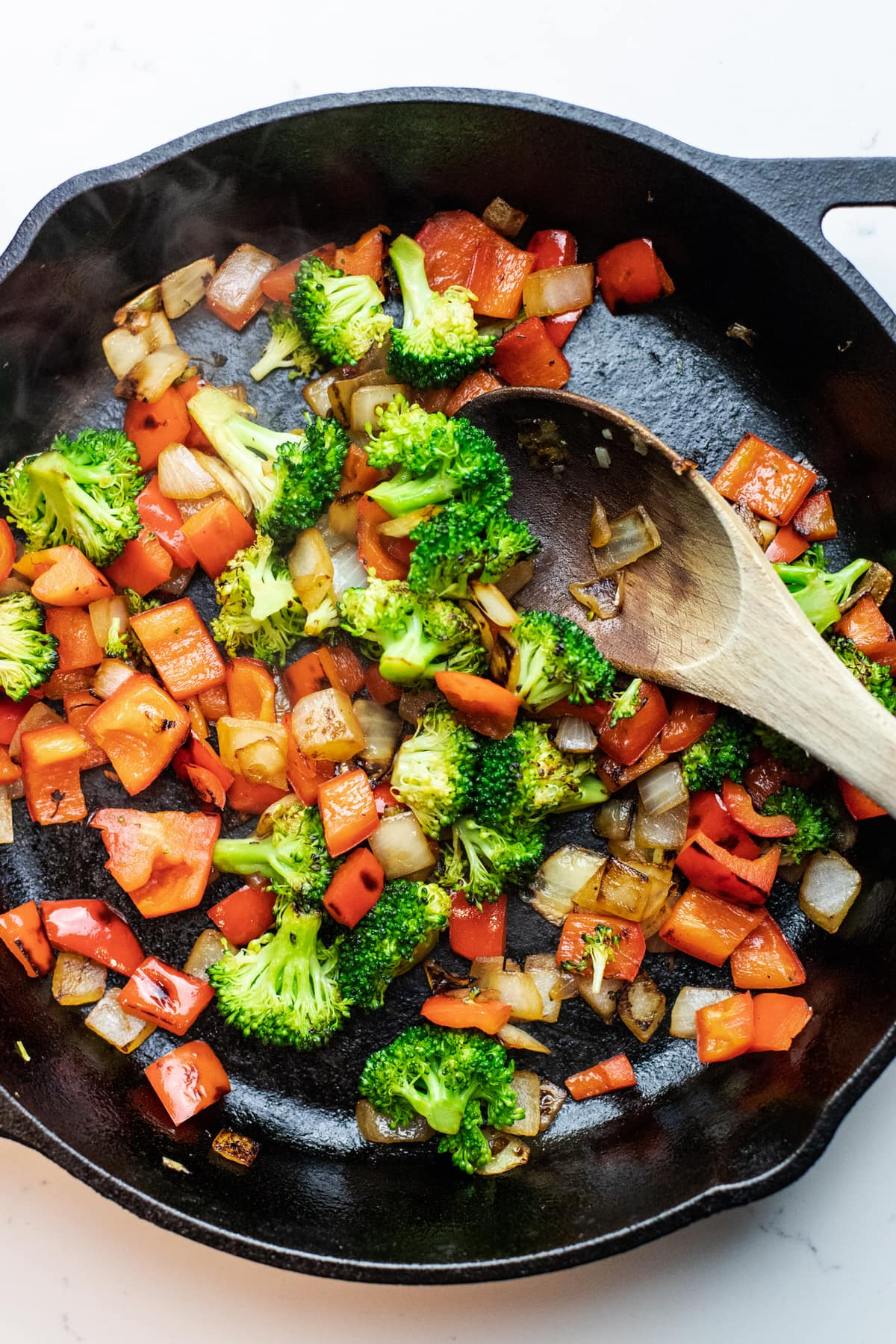 vegetables sauteed in a black skillet with a wooden spoon.