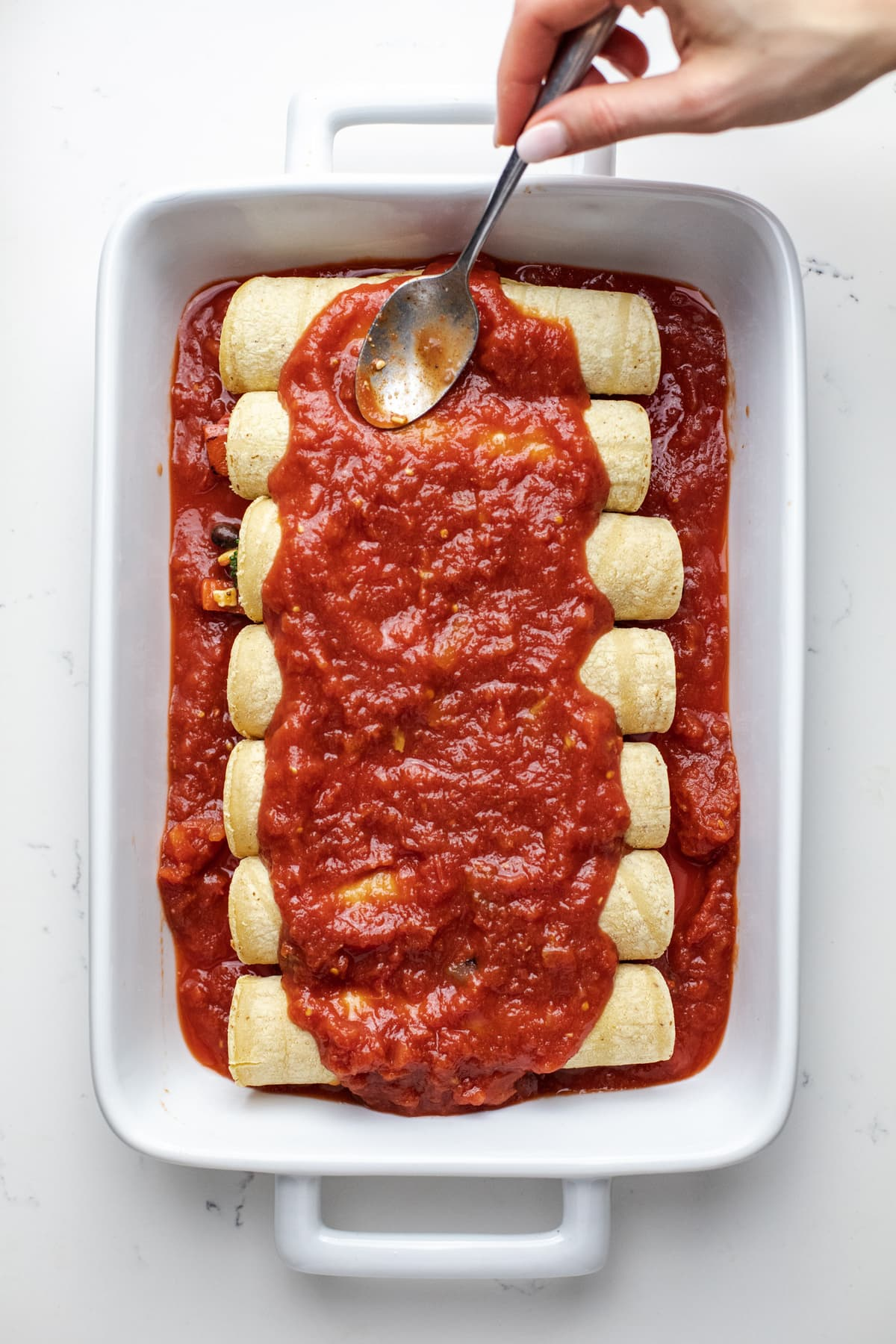 Enchiladas in a white dish with red sauce over top.