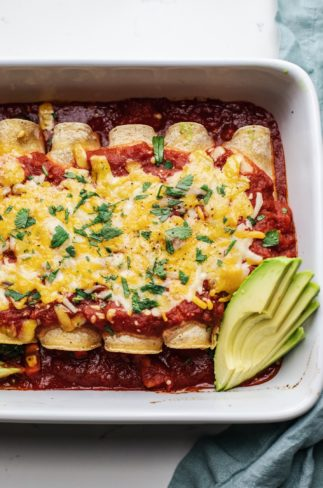 Baked enchiladas in a white dish with avocado slices on the side.