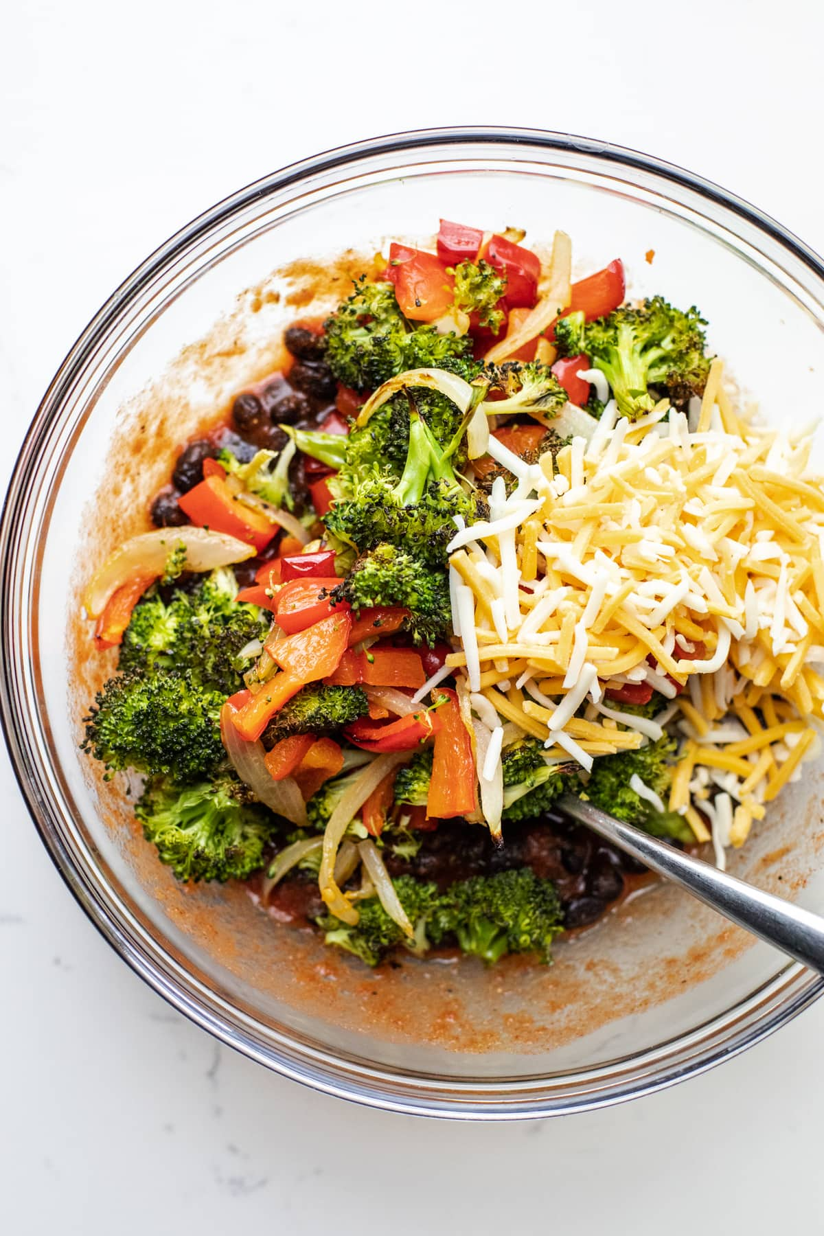 A bowl of vegetable filling for enchiladas in a glass bowl.