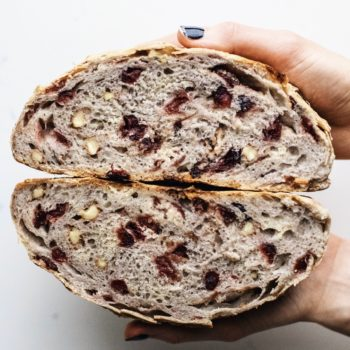 Hands holding two halves of cranberry walnut bread.