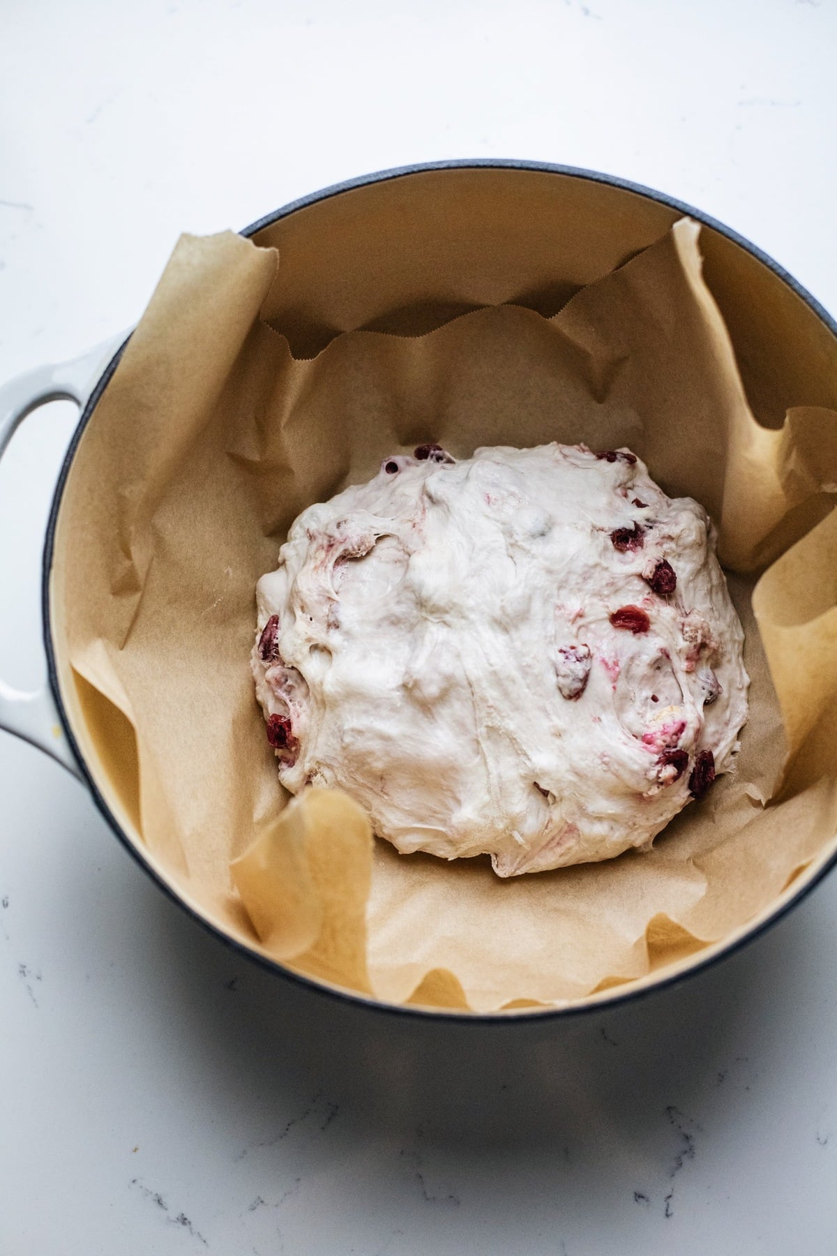 A ball of dough in a white pot with parchment paper.
