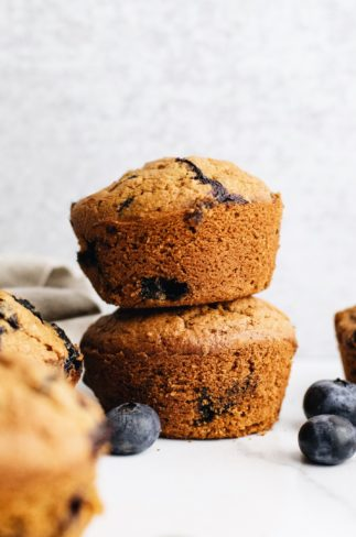 two muffins stacked on top of each other with blueberries and muffins scattered around them.