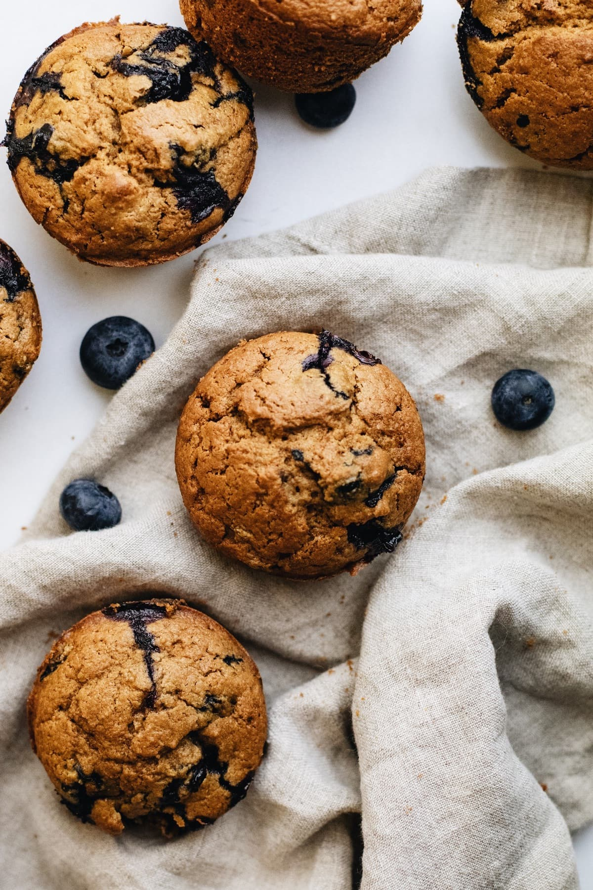 Blueberry muffins on a grey napkin with blueberries scattered around.