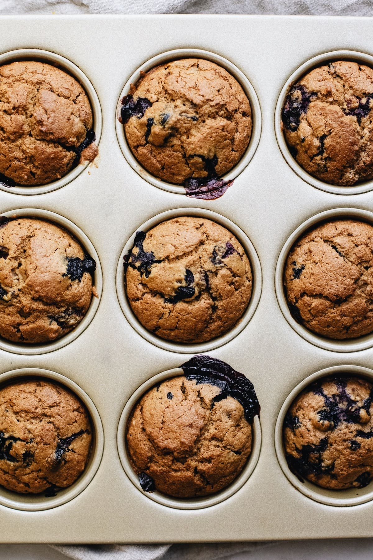 baked blueberry muffins in a muffin tin.
