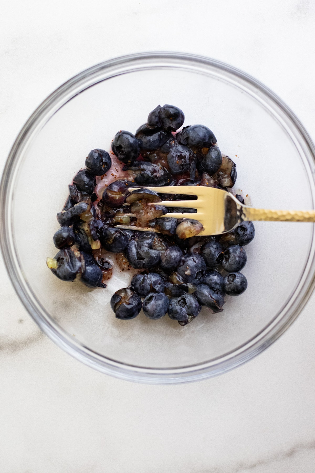 A fork mashing blueberries in a clear glass bowl.