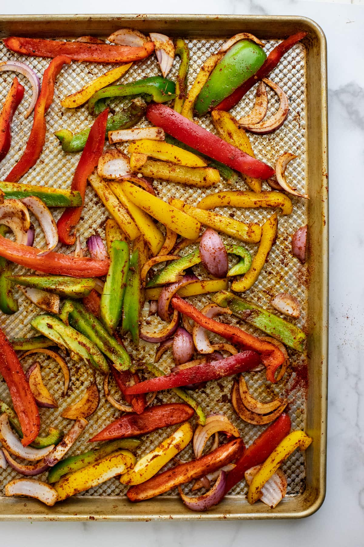 Copper sheet pan with roasted colored black peppers on it.