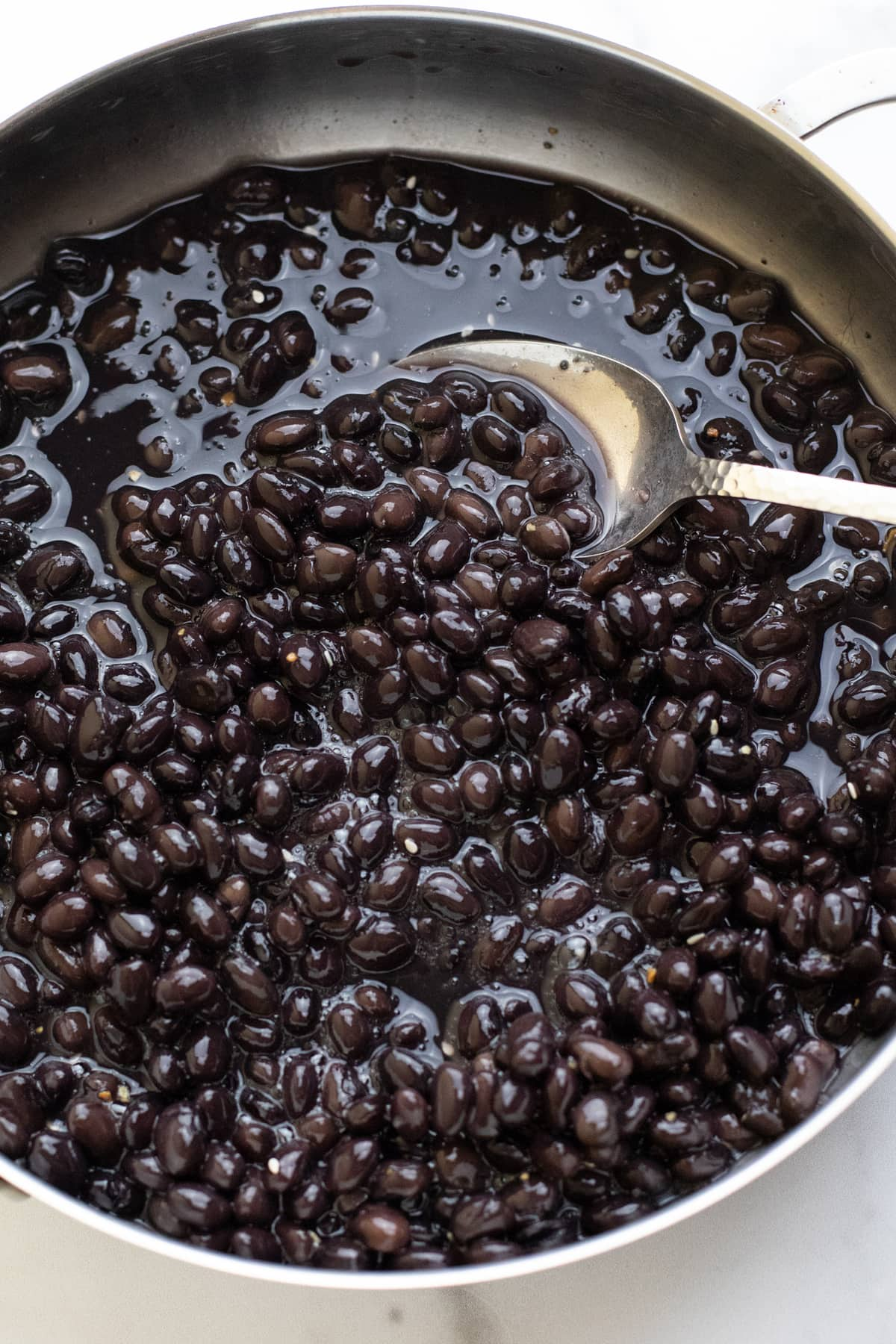 Spoon stirring black beans in a silver pan.