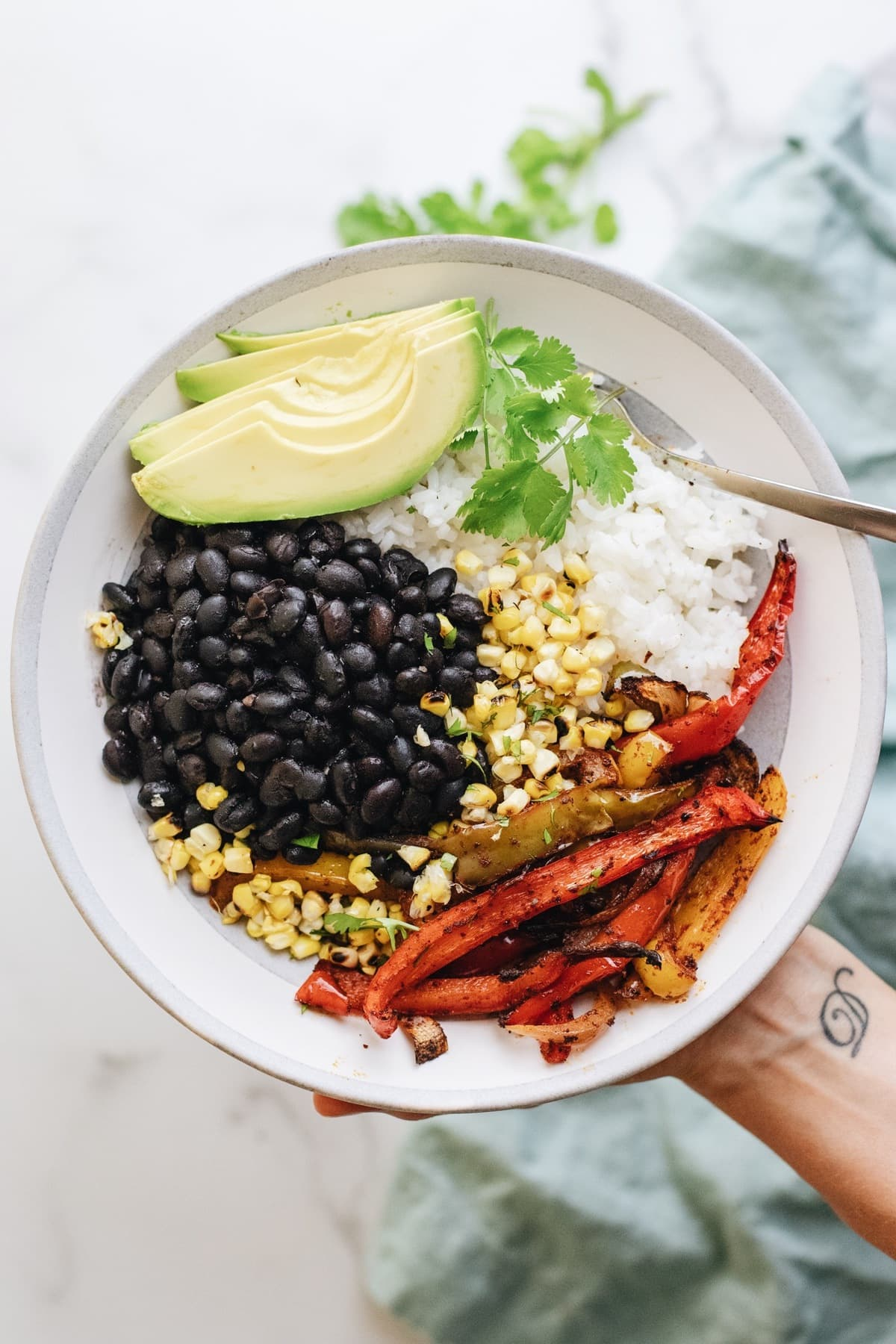 A hand holding a ceramic bowl with black beans, rice, and vegetables.